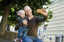 Padre e hijo bebé fotografiándose a sí mismos con un teléfono inteligente - foto de stock