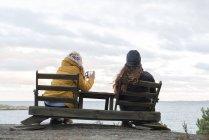 Vista posteriore di giovani donne sedute su sedie di legno sul lago e scattare foto — Foto stock