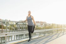 Young woman doing exercises on bridge — Stock Photo