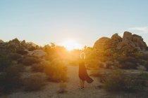 Жінка носить плаття походи в Національний парк Джошуа Tree на заході сонця — стокове фото