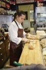 Вид збоку жінка різання хліба в магазині — стокове фото