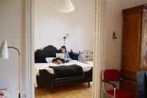 Woman using laptop on bed, view through doorway — Stock Photo