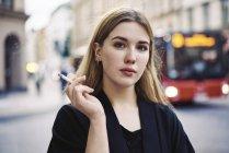 Portrait de jeune femme fumant dans la rue — Photo de stock