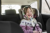 Girl dressed up as Easter witch wearing headscarf laughing in car — Stock Photo