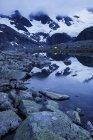 Vue panoramique de la gamme Jotunheimen Sentraltind pic, couple camping en arrière-plan — Photo de stock