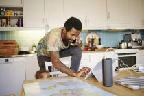 Father with baby son using mobile devices at kitchen — Stock Photo