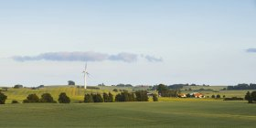 Panoramic view of green fields with wind turbine under blue sky — Stock Photo