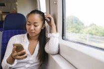 Woman sitting on train and looking on smartphone — Stock Photo