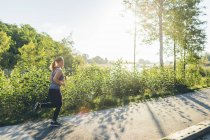 Young woman jogging on pavement in sunlight — Stock Photo