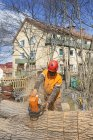 Arborist in protective workwear cutting log — Stock Photo