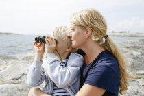 Мать и сын сидят на скалистом берегу, сын смотрит в бинокль на Стокгольмском архипелаге — стоковое фото