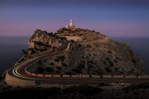 Lighthouse on edge of cliff at dusk, Cap Formentor, Spain — Stock Photo