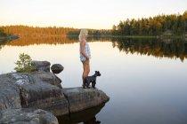 Женщина и собака смотрят на вид со стороны озера — стоковое фото