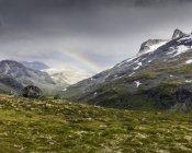 Jotunheimen Bereich und saftig grünes Tal mit Regenbogen im Himmel — Stockfoto