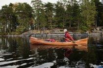 Side view of man paddling canoe on lake — Stock Photo