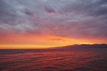 Paysage marin avec des silhouettes de montagnes sur le ciel couchant — Photo de stock