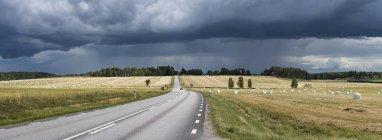 Nuvens de tempestade no céu ao longo da estrada do país — Fotografia de Stock