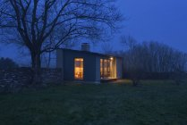 Illuminated small modern house at night — Stock Photo