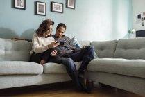 Pareja joven sentada en el sofá y mirando el teléfono inteligente - foto de stock