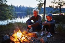 Mother and daughter by a campfire, selective focus — Stock Photo