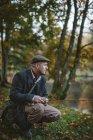 Visão lateral do homem que pesca no rio, foco em primeiro plano — Fotografia de Stock