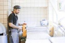 Пекарь с тестом для хлеба на кухне — стоковое фото