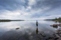 Vue arrière de l'homme debout sur des rochers au bord du lac — Photo de stock