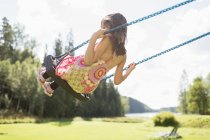 Rear view of girl on swing, selective focus — Stock Photo