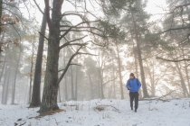 Man walking through snowy forest, selective focus — Stock Photo