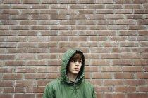 Portrait d'homme regardant loin contre un mur de briques — Photo de stock