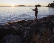 Homme adulte moyen pêchant au coucher du soleil — Photo de stock