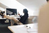 Empresária com os pés na mesa, foco seletivo — Fotografia de Stock