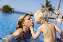 Mother kissing son in swimming pool, focus on foreground — Stock Photo