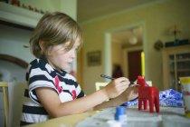 Garçon peinture jouet de cheval, foyer sélectif — Photo de stock
