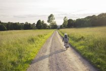 Chico ciclismo distancia por camino de tierra a través de campos - foto de stock