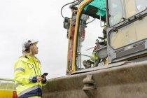 Женщина разговаривает с мужчиной на стройке, дифференциальный фокус — стоковое фото