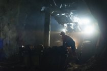 Miner in protective workwear working underground — Stock Photo