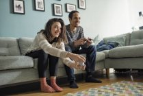 Young couple playing video games in living room — Stock Photo