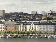 Stadtbild am Wasser mit im Vordergrund vertäfelten Schiffen — Stockfoto