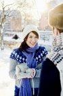 Jeune femme portant un chapeau en tricot et des gants tenant du chocolat chaud — Photo de stock