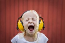 Ritratto di ragazza bionda che indossa i manicotti delle orecchie, urlando con gli occhi chiusi — Foto stock