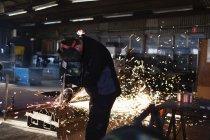 Юнак різання металу в майстерні — стокове фото