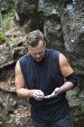 Человек с руками в щелочном порошке против камня — стоковое фото