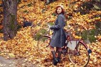 Ritratto di donna in piedi con bicicletta in parco in autunno — Foto stock