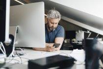 Geschäftsmann nutzt Smartphone am Schreibtisch — Stockfoto