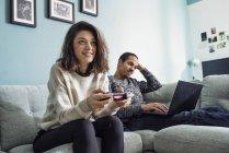 Девушка, играющая в видеоигры, и молодой человек, использующий ноутбук в гостиной — стоковое фото