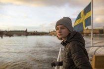 Garçon sur le bateau avec le drapeau suédois, se concentrer sur le premier plan — Photo de stock