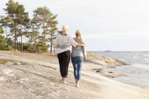 Rear view of two women walking barefoot along rocks by sea — Stockfoto