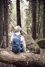 Female backpacker sitting on trunk of fallen tree in forest — Stock Photo