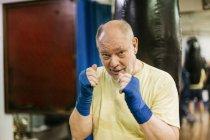 Senior man with fists raised at boxing training — Stock Photo